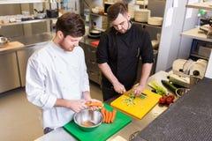 Счастливый мужской шеф-повар варя еду на кухне ресторана Стоковая Фотография RF