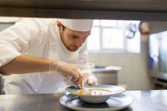 Счастливый мужской шеф-повар варя еду на кухне ресторана Стоковые Фотографии RF