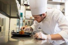 Счастливый мужской шеф-повар варя еду на кухне ресторана Стоковое Изображение RF