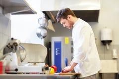Счастливый мужской шеф-повар варя еду на кухне ресторана Стоковые Фото