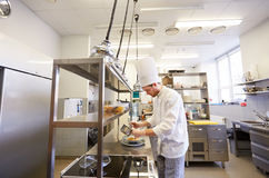 Счастливый мужской шеф-повар варя еду на кухне ресторана Стоковое Фото