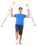 Счастливый мужчина с сломленной ногой используя костыль Стоковое Фото