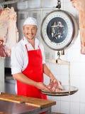 Счастливый мясник веся мясо на масштабе стоковое фото