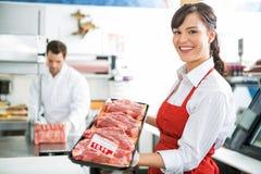 Счастливый мясник держа поднос мяса в магазине стоковые изображения rf