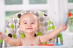 Счастливый младенец ест с ложкой и вилкой стоковое фото