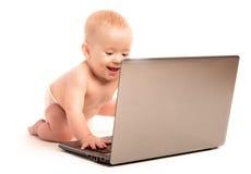 Счастливый младенец и изолированный портативный компьютер