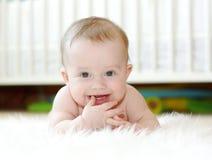 Счастливый младенец против белой кровати стоковое фото