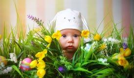 Счастливый младенец ребенка одетый как кролик зайчика пасхи на траве Стоковое Изображение RF