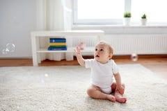 Счастливый младенец с пузырями мыла дома Стоковая Фотография RF