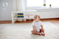 Счастливый младенец с пузырями мыла дома Стоковое Изображение RF
