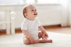 Счастливый младенец с пузырями мыла дома Стоковая Фотография