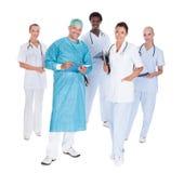 Счастливый доктор в хирургической мантии с его сотрудниками Стоковое фото RF