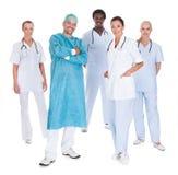 Счастливый доктор в хирургической мантии с его сотрудниками Стоковые Фото