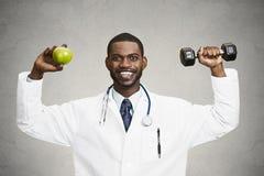 Счастливый доктор держа зеленое яблоко, гантель Стоковые Фото
