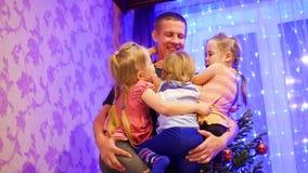 Счастливый отец держит на руках детей, усмехаясь и смеясь над в вечере рождества На заднем плане, света и сток-видео