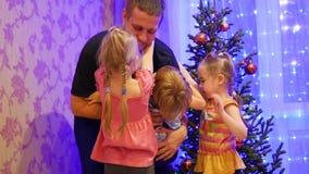 Счастливый отец держит на руках детей, усмехаясь и смеясь над в вечере рождества На заднем плане, света и видеоматериал