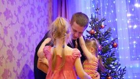 Счастливый отец держит на руках детей, усмехаясь и смеясь над в вечере рождества На заднем плане, света и акции видеоматериалы