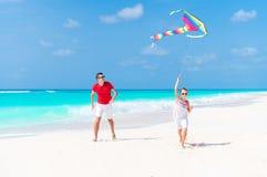 Счастливый отец и милый маленький змей летания дочери совместно на тропическом пляже Стоковая Фотография