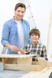 Счастливый отец и сын делая реновацию Стоковое Изображение