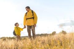 Счастливый отец идя на луг с его ребенком Стоковое Изображение RF