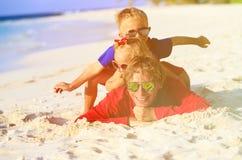 Счастливый отец при 2 дет имея потеху на песке Стоковые Фото