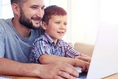 Счастливый отец при сын играя компютерные игры на компьтер-книжке Стоковая Фотография RF