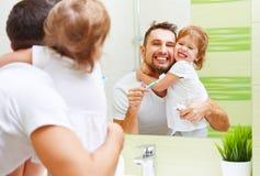 Счастливый отец семьи и девушка ребенка чистя ее зубы щеткой в bathroo Стоковая Фотография