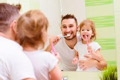 Счастливый отец семьи и девушка ребенка чистя ее зубы щеткой в bathroo Стоковая Фотография RF