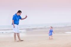Счастливый отец с его дочерью малыша на пляже стоковые фото