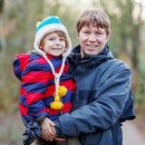 Счастливый отец с его сыном на руке outdoors Стоковые Изображения
