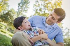 Счастливый отец щекоча сына в парке Стоковая Фотография