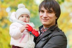 Счастливый папа держа младенца на предпосылке ландшафта осени стоковая фотография rf