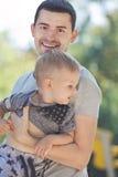 Счастливый папа идя с младенцем в его оружиях стоковые изображения