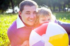 Счастливый папа с ее дочерью outdoors в солнечном свете Стоковая Фотография