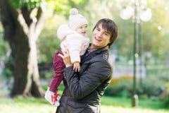 Счастливый папа с дочерью на его оружиях в осени паркует стоковое фото rf