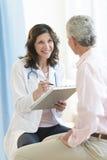 Счастливый пациент доктора С Доски сзажимом для бумаги Looking На Стоковые Изображения