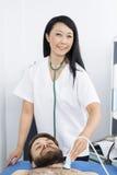 Счастливый пациент доктора Performing Ультразвука Испытания На Стоковое фото RF