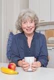 Счастливый пенсионер на кухонном столе Стоковое фото RF