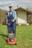 Счастливый пожилой человек с травокосилкой стоковые изображения rf