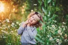 Счастливый портрет девушки ребенка на поле захода солнца лета с цветками Стоковое Изображение RF