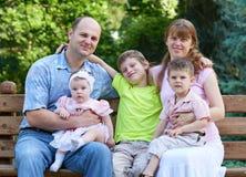 Счастливый портрет на внешнем, группа в составе семьи 5 людей сидит на деревянной скамье в парке города, сезоне лета, ребенке и р Стоковая Фотография