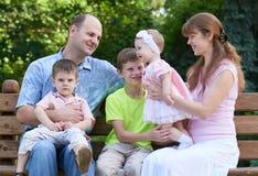 Счастливый портрет на внешнем, группа в составе семьи 5 людей сидит на деревянной скамье в парке города, сезоне лета, ребенке и р Стоковые Изображения RF