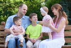 Счастливый портрет на внешнем, группа в составе семьи 5 людей сидит на деревянной скамье в парке города, сезоне лета, ребенке и р Стоковое Изображение RF