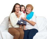 Счастливый портрет семьи - младенец, женщина и пожилая женщина на белизне Стоковое фото RF