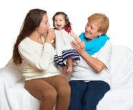 Счастливый портрет семьи - младенец, женщина и пожилая женщина на белизне Стоковое Изображение