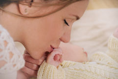 Счастливый поцелуй матери вручает ее newborn младенца Стоковая Фотография RF