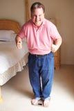 Счастливый полный человек стоя на масштабах в спальне стоковая фотография rf