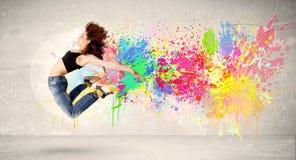Счастливый подросток скача с красочным splatter чернил на городском backg Стоковые Фото