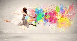 Счастливый подросток скача с красочным splatter чернил на городском backg Стоковое Фото