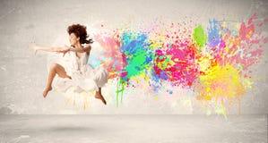 Счастливый подросток скача с красочным splatter чернил на городском backg Стоковая Фотография RF
